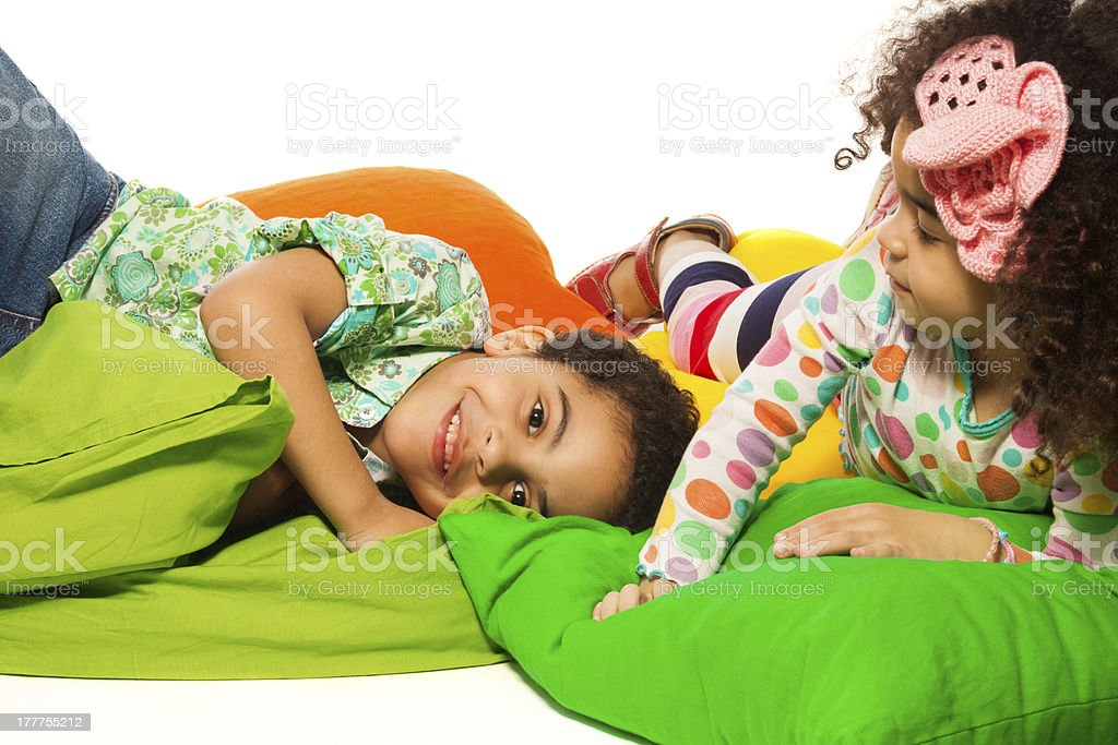 Black boy and girl playing with pillows royalty-free stock photo