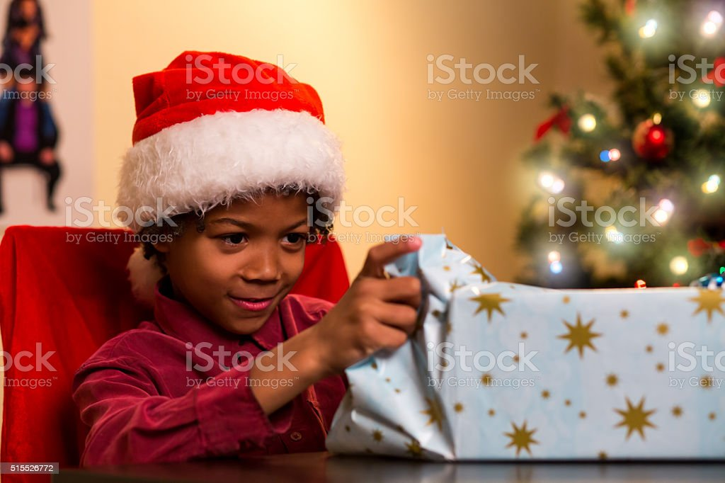 Black boy opening Christmas present. stock photo