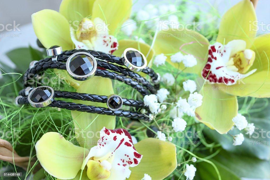 Black bracelet with orchids stock photo