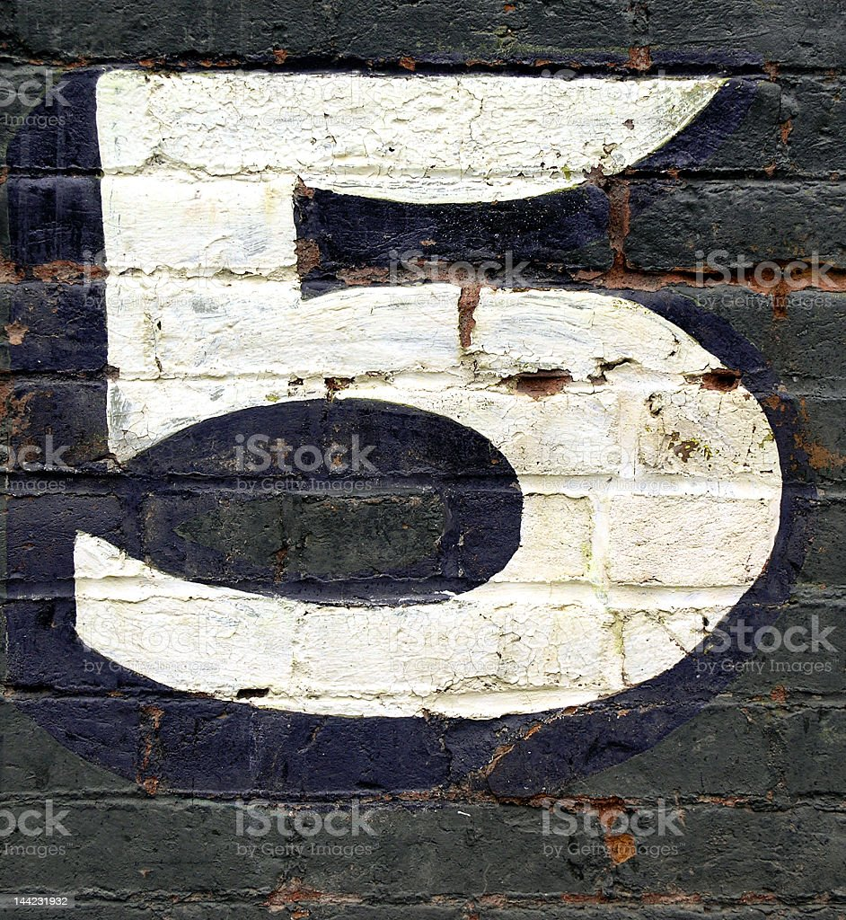 Black brick wall with the number five painted on it in white stock photo
