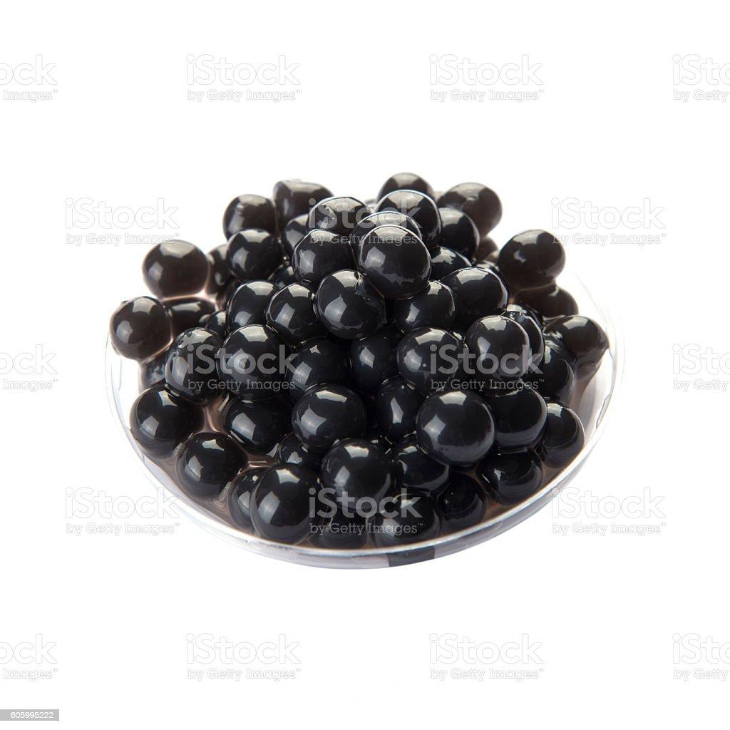 Black bubble tea tapioca pearls in plastic container stock photo