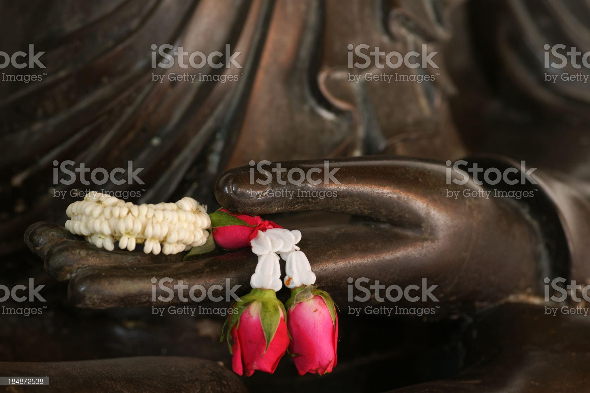 Black Buddha statue and garland on hand, Thailand royalty-free stock photo