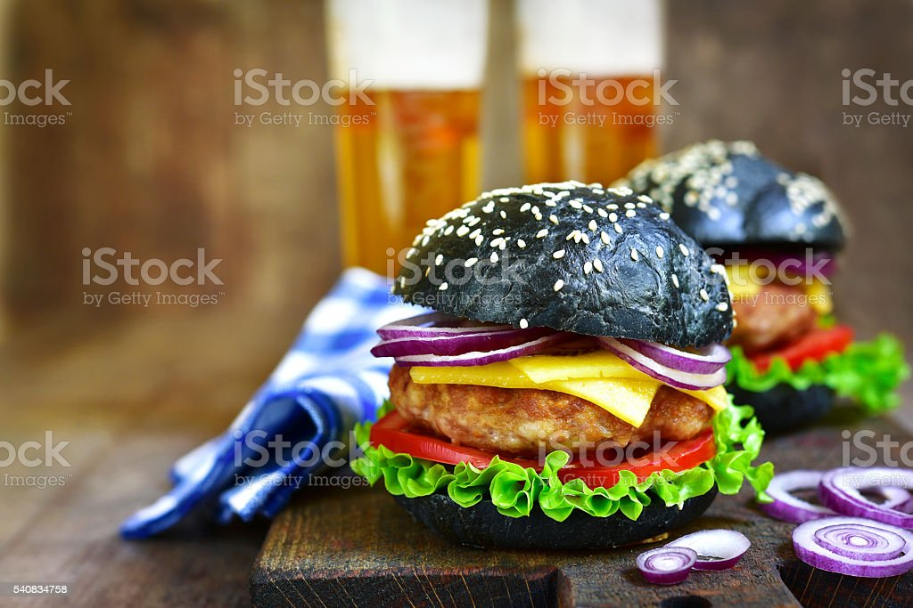 Black burger with meat cutlet on a cutting board.Rustic style. stock photo