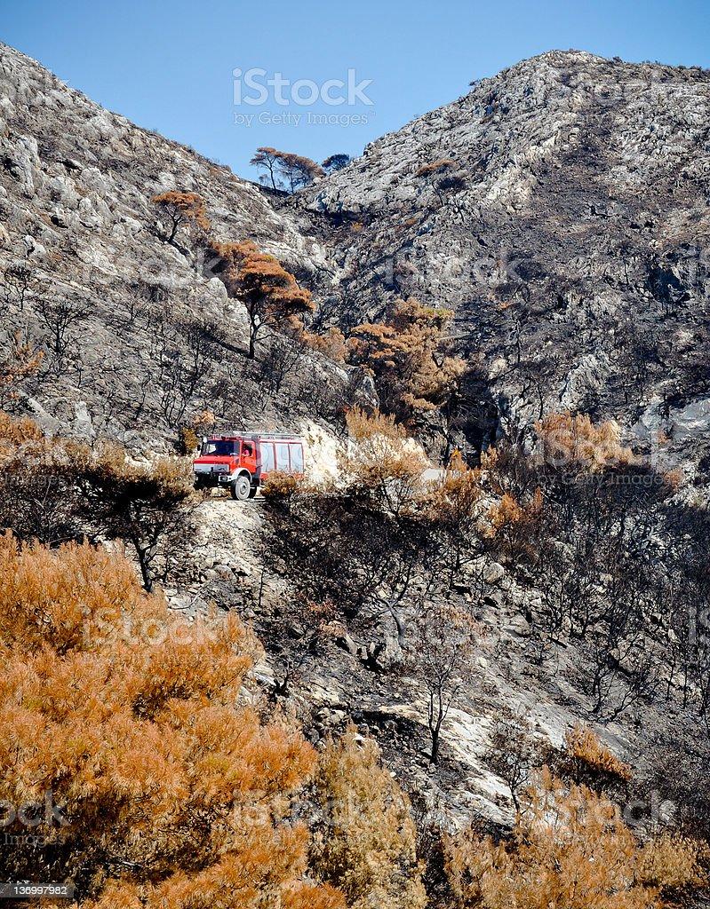 Schwarzes gebranntes land, Feuerwehrauto und blauem Himmel Lizenzfreies stock-foto