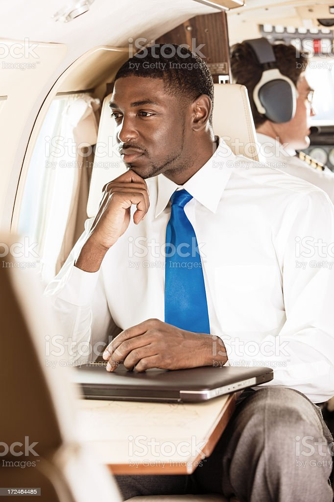 Black Businessman Looking Out Window of Private Jet royalty-free stock photo