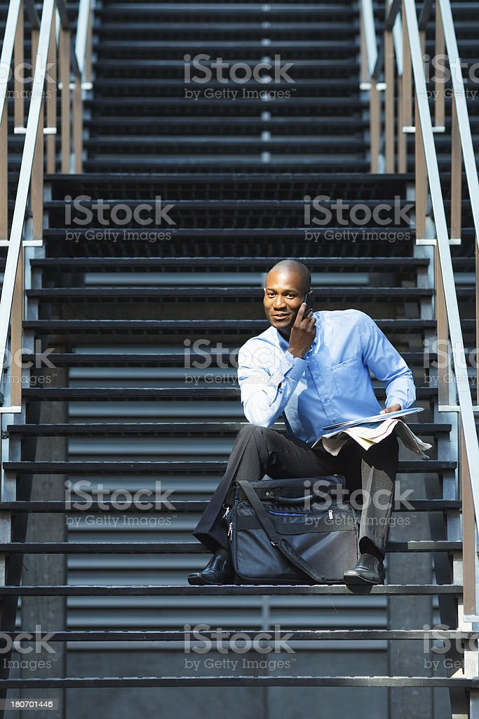 Black businessman on the phone sitting in stairs vertical royalty-free stock photo