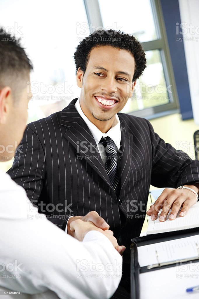 Black Businessman shaking hands with colleague in office royalty-free stock photo
