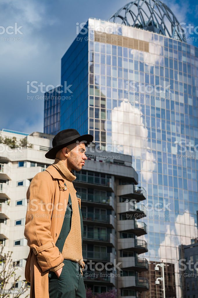 black businessman stands outside skyscraper in financial district stock photo