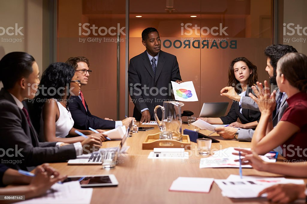 Black businessman stands to present to colleagues at meeting stock photo