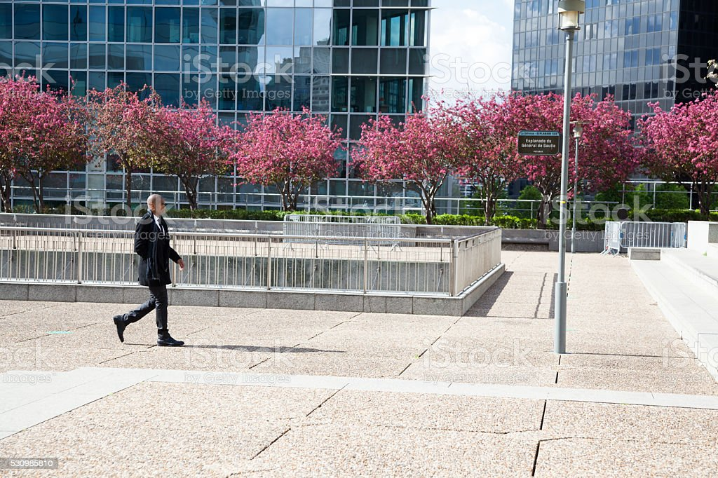 black businessman walking across plaza in financial district sunny day stock photo
