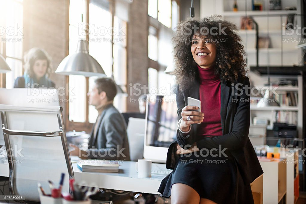 Black businesswoman using cell phone in the office stock photo
