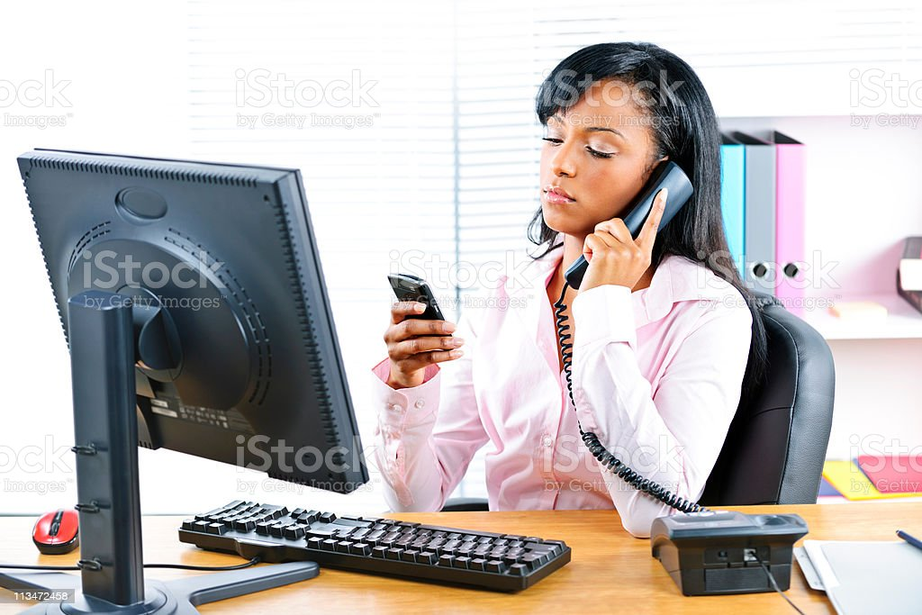 Black businesswoman using two phones at desk royalty-free stock photo