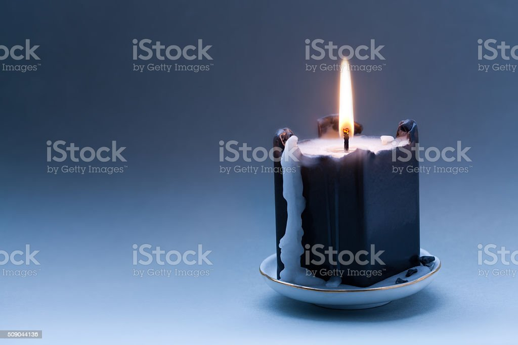 Black candle with a flame and drips. Dark blue gradient stock photo