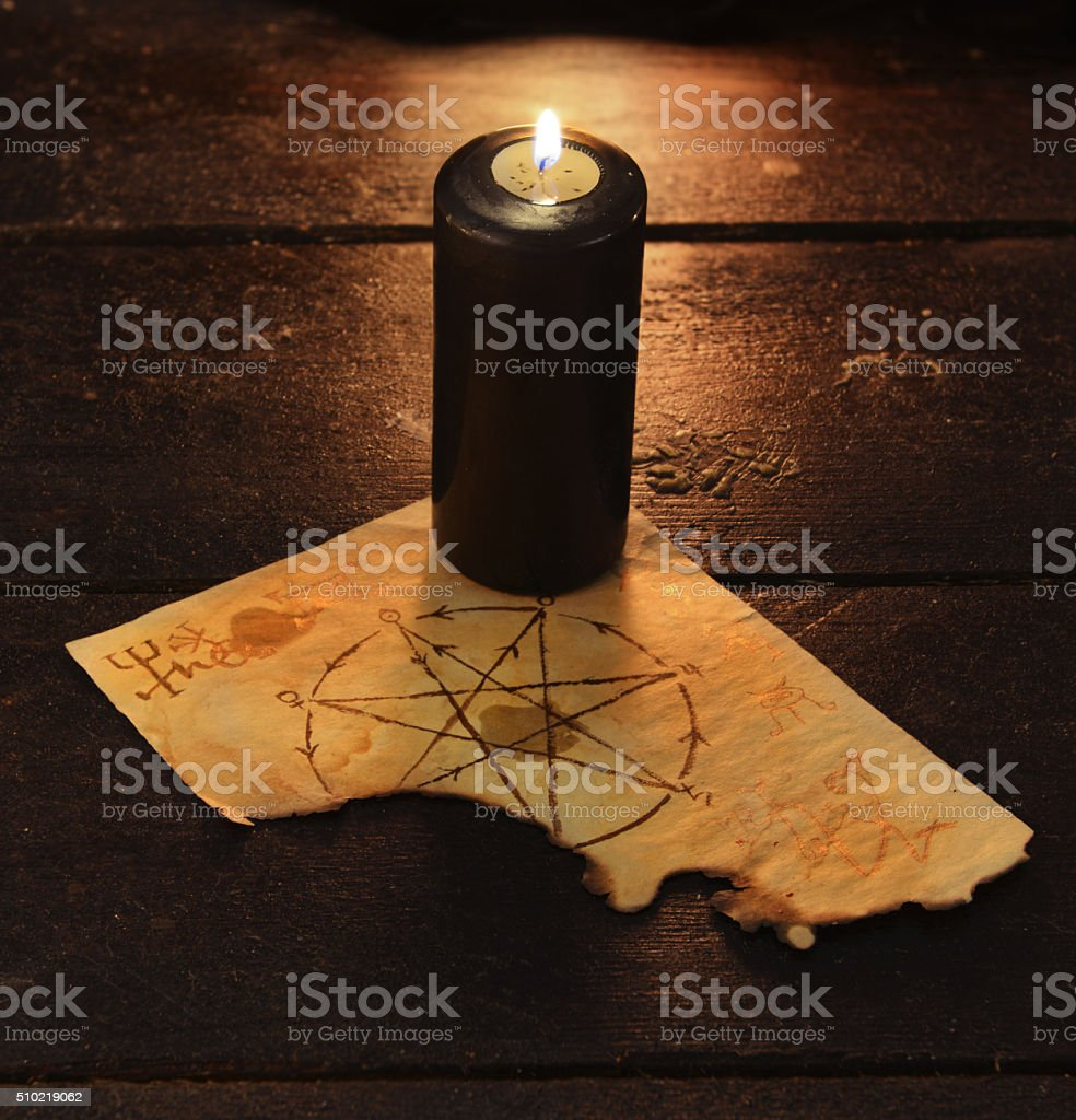Black candle with pentagram stock photo