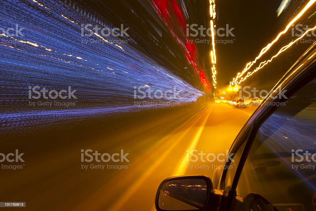 A black car driving on a lit up tunnel at night royalty-free stock photo