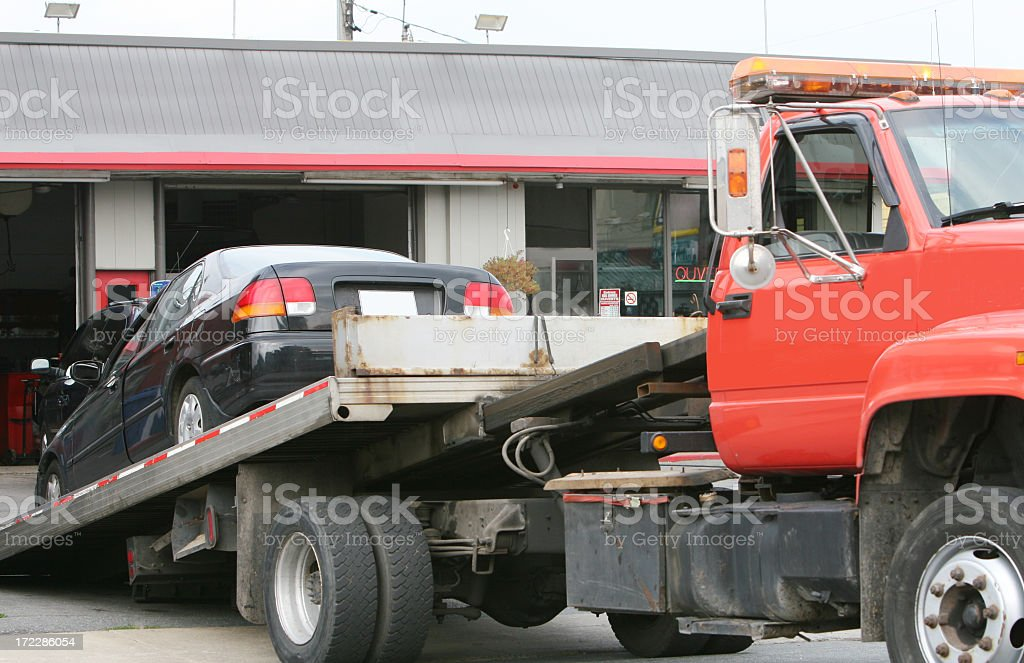 Black car on a red flat bed tow truck stock photo