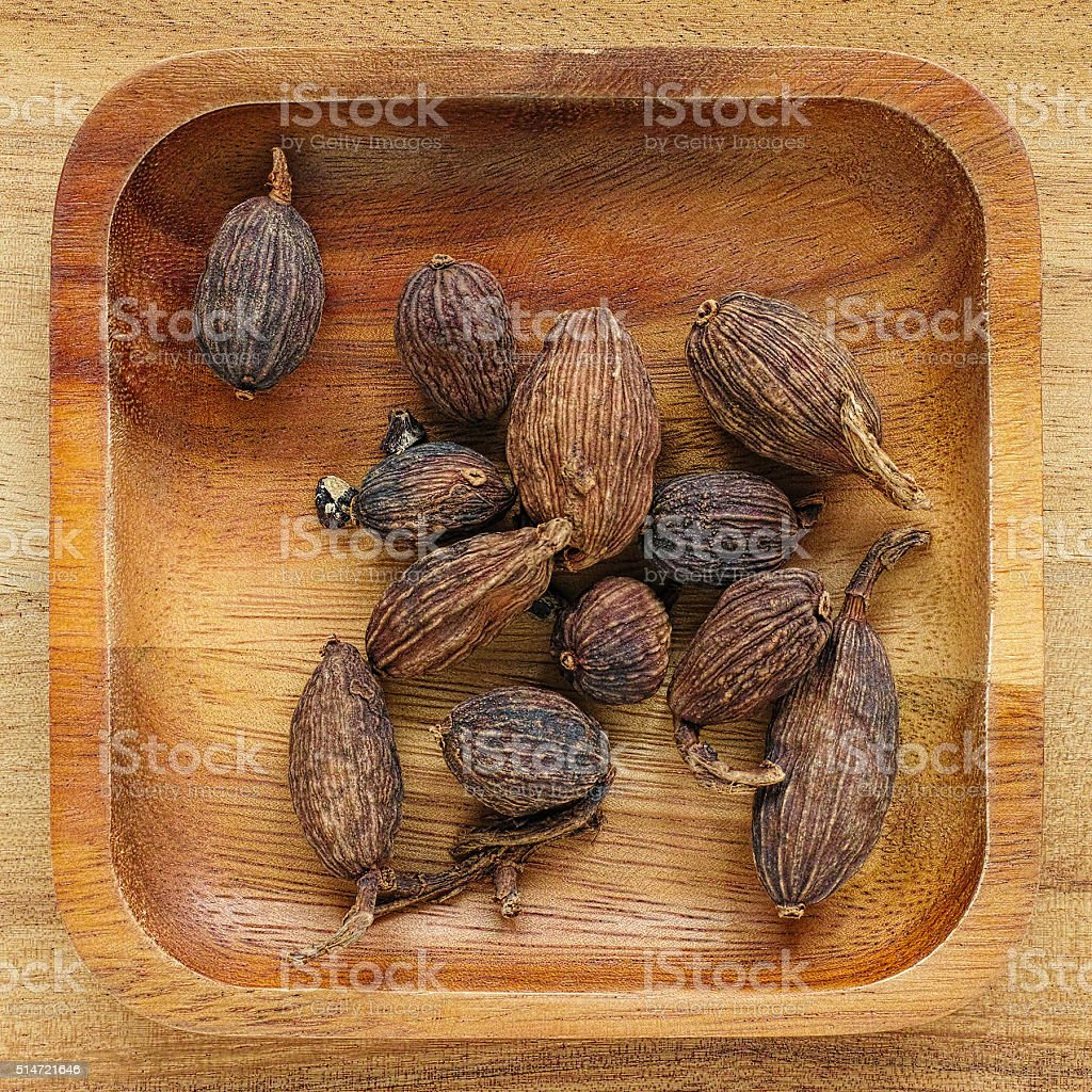 Black Cardamom in a wooden tray. stock photo