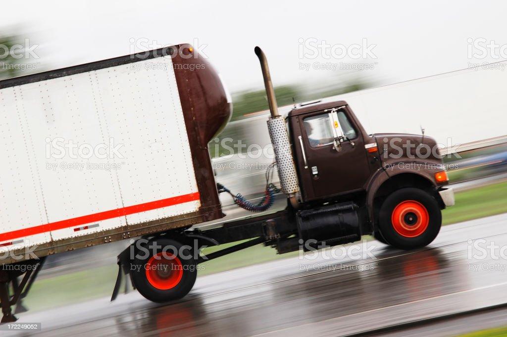 Black cargo truck speeding in the road stock photo