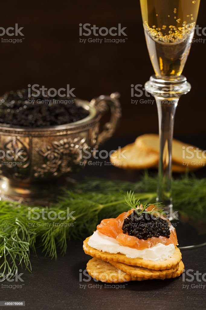 Black caviar served on crackers with salmon and cream cheese. stock photo