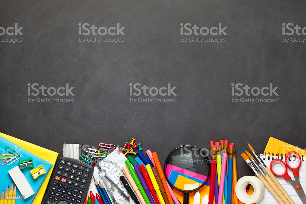 Black chalkboard with school supplies at the bottom border stock photo