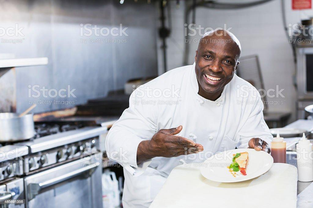 Black chef in a restaurant holding dessert plate stock photo