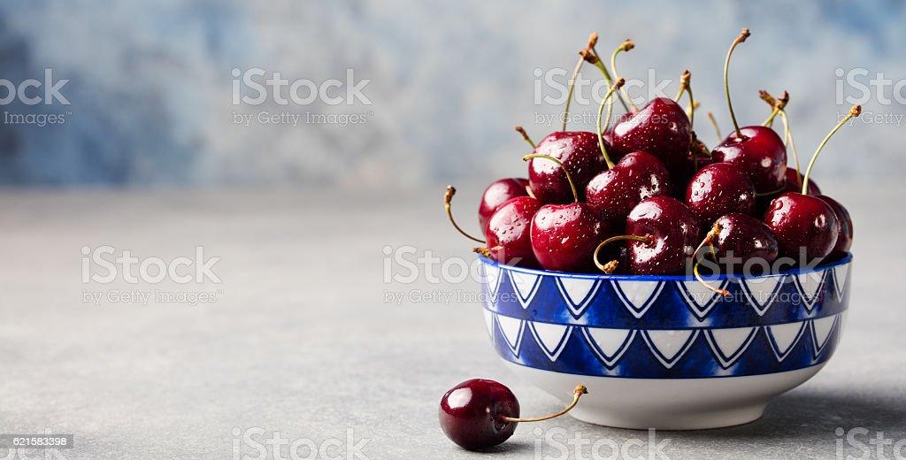 Black cherries in black bowl Grey stone background Copy space stock photo
