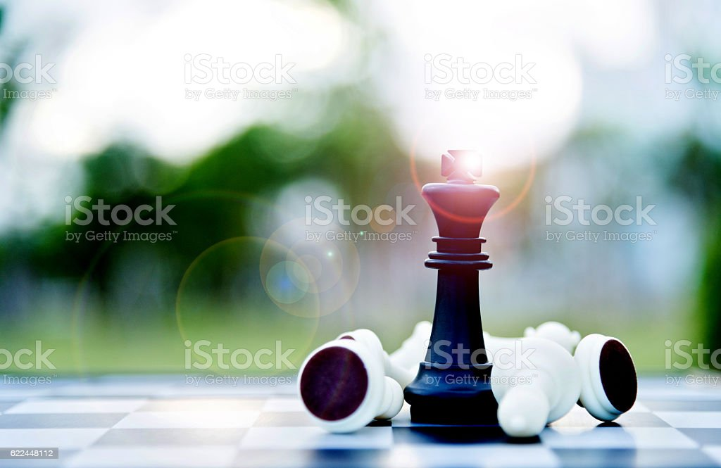 Black chess king among lying down white pawns stock photo