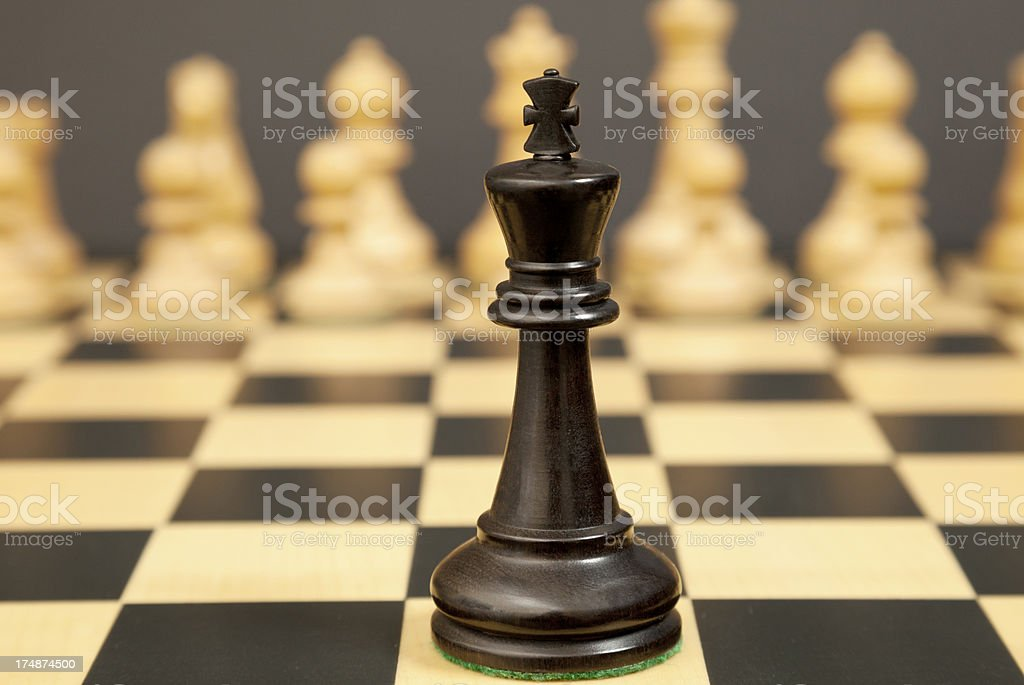 Black chess king faces white opponents stock photo