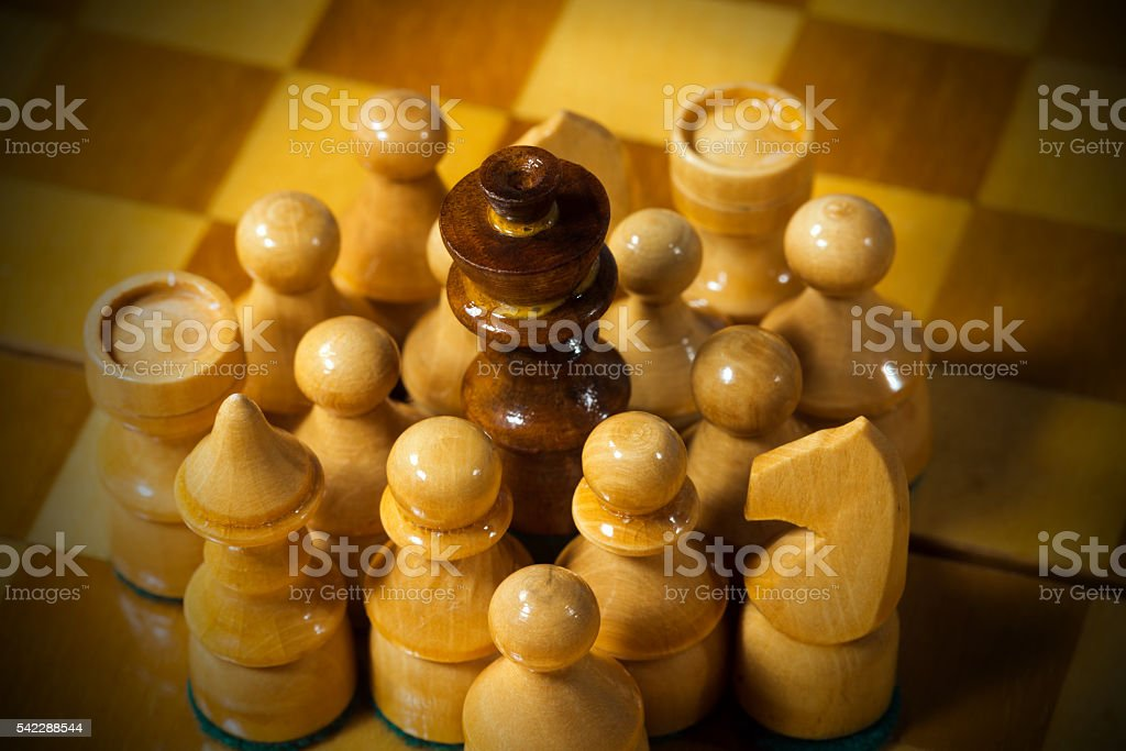 Black Chess King Surrounded by White Pieces stock photo