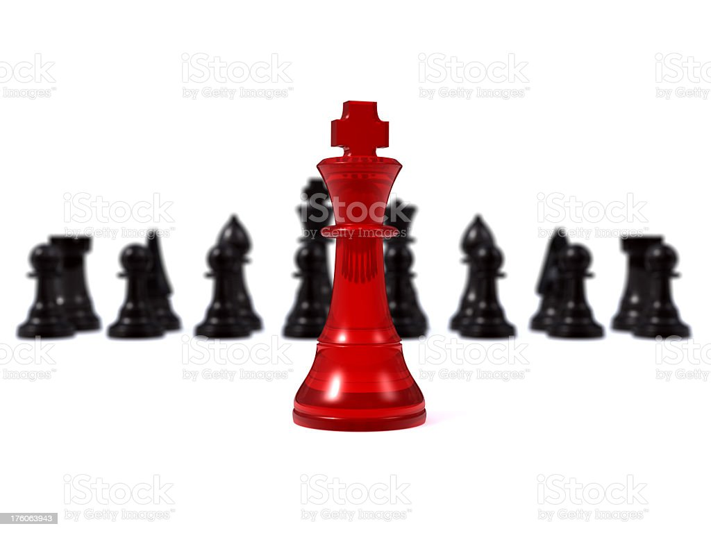 Black chess pieces behind a lone red chess piece stock photo