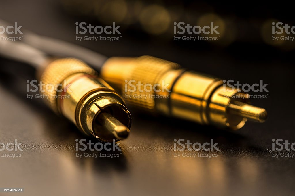 Black cinch audio cable with golden plugs macro on black stock photo