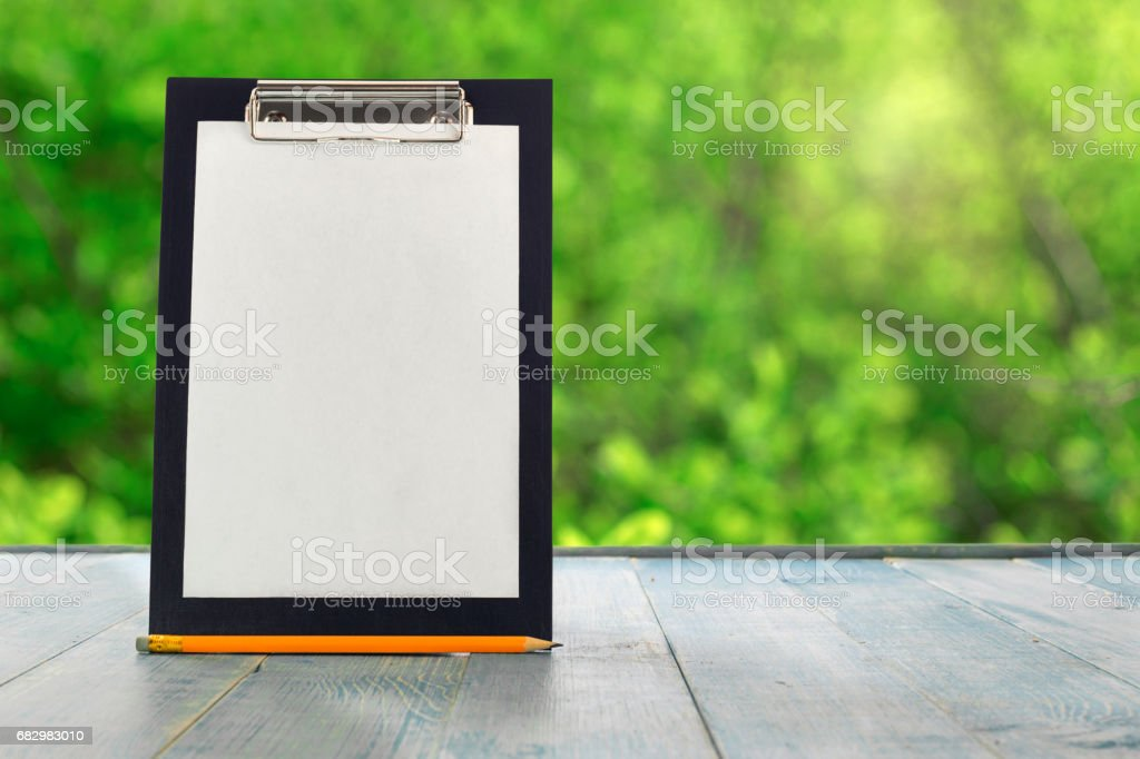 Black clipboard with pencil on a blue wooden table stock photo