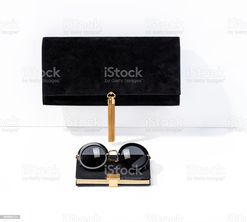 Black clutch bag and sunglasses with notebook isolated on white background stock photo