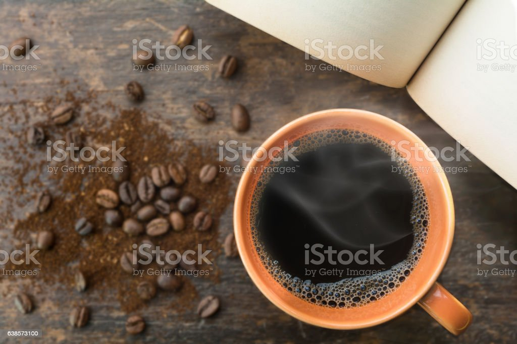 Black coffee cup  and coffee beans with open old  book stock photo