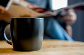 black coffee cup on table, reading