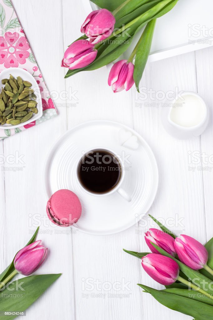 Black coffee in a white cup, cardamom, pink spring tulips and raspberry macaron or macaroon on a wooden background. Top view stock photo