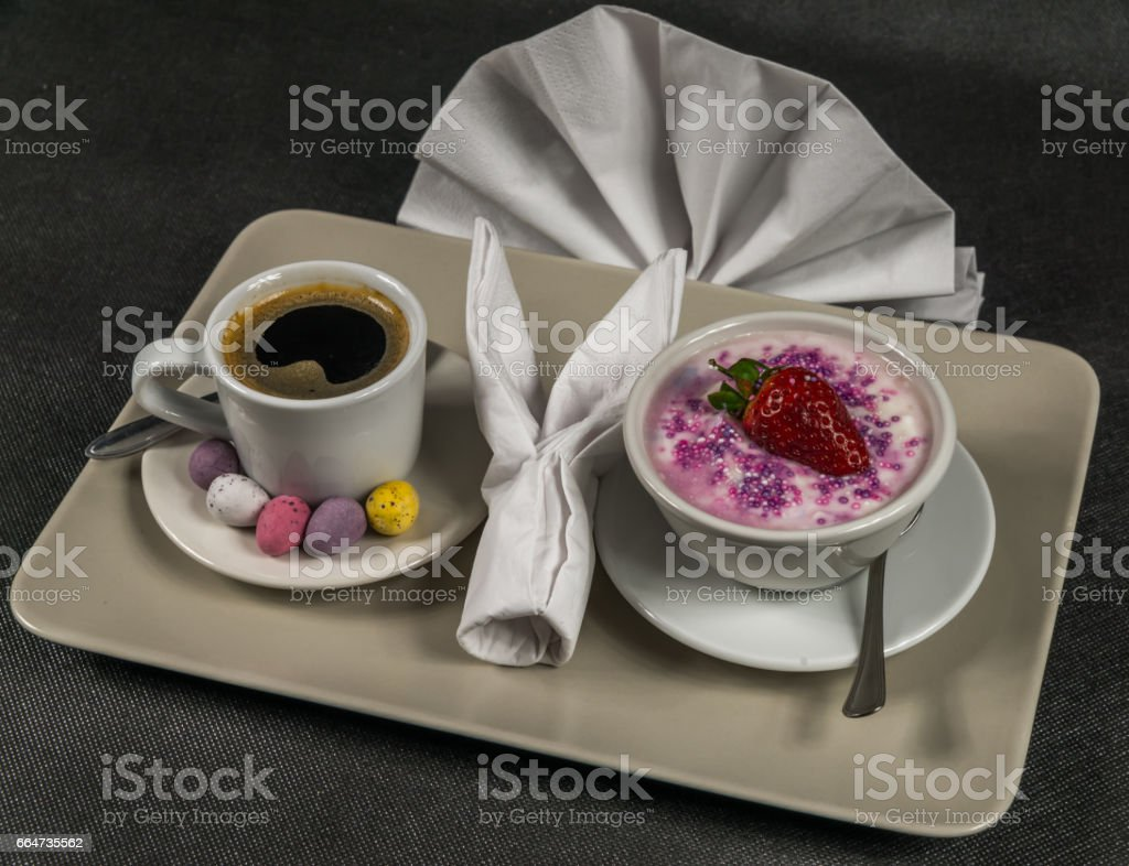 black coffee in a white cup, dessert, yogurt with a large strawberry and sprinkles, on a gray plate, napkin stock photo