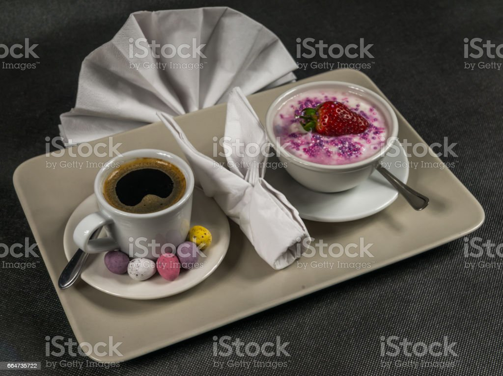 black coffee in a white cup, dessert, yogurt with a large strawberry and sprinkles, on a gray plate, napkin, sweet eggs, stock photo