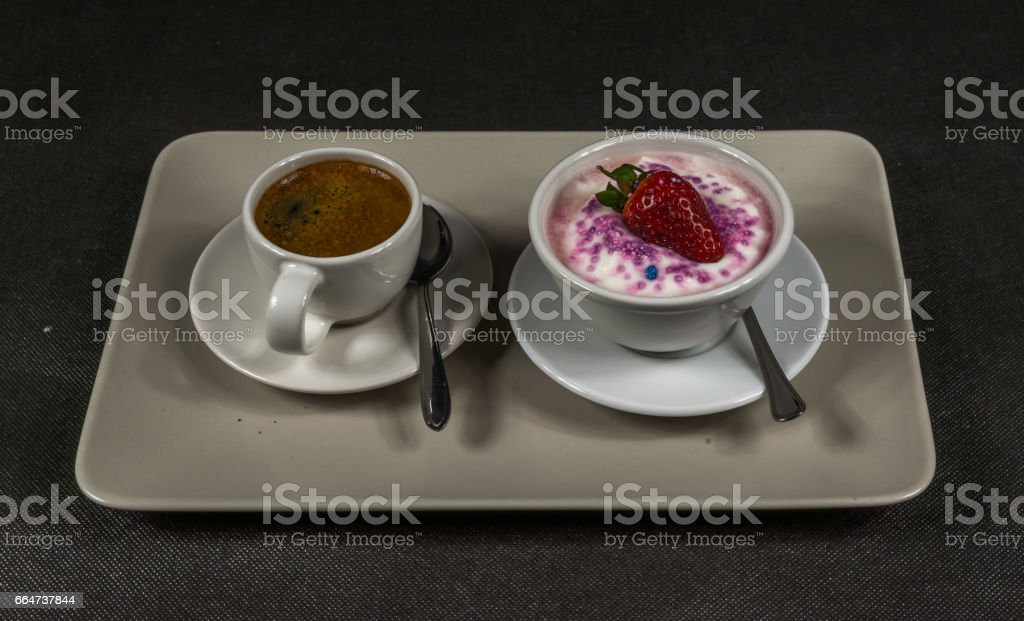 black coffee in a white cup, dessert, yogurt with a large strawberry and sprinkles, on a gray plate stock photo