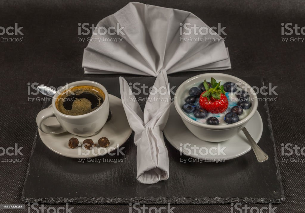 black coffee in a white cup, dessert, yogurt with a large strawberry and blueberries, on a black stone plat stock photo