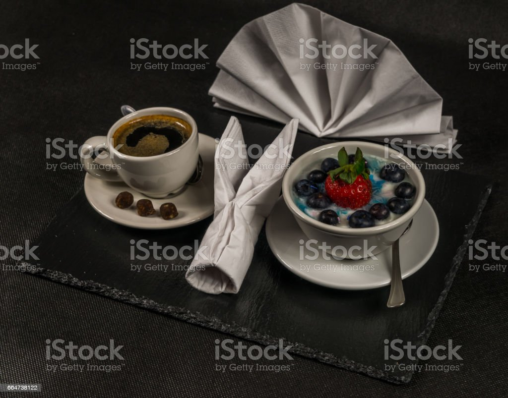 black coffee in a white cup, dessert, yogurt with a large strawberry and blueberries, on a black stone plate stock photo