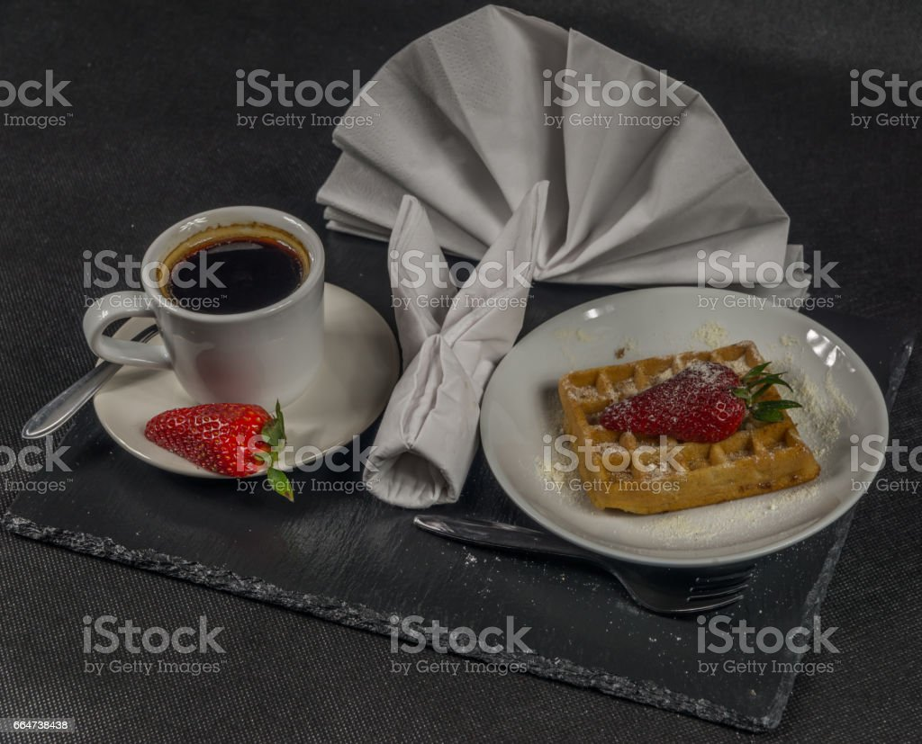 black coffee in a white cup, waffle with strawberries and powdered sugar, black fork, napkin stock photo