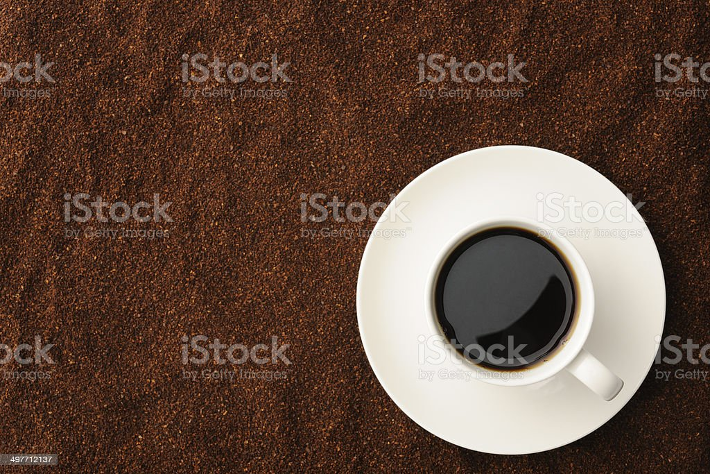 Black coffee in white coffee cup against ground coffee beans royalty-free stock photo