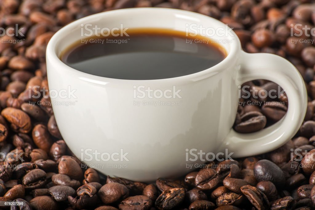 Black coffee in white cup, against a background of brown coffee beans, coffee background, aromatic coffee stock photo