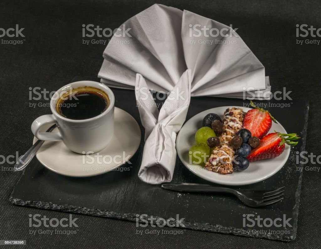 black coffee in white cup, healthy, energetic breakfast, bar whole grain, grapes, strawberries and blueberries, napkin stock photo