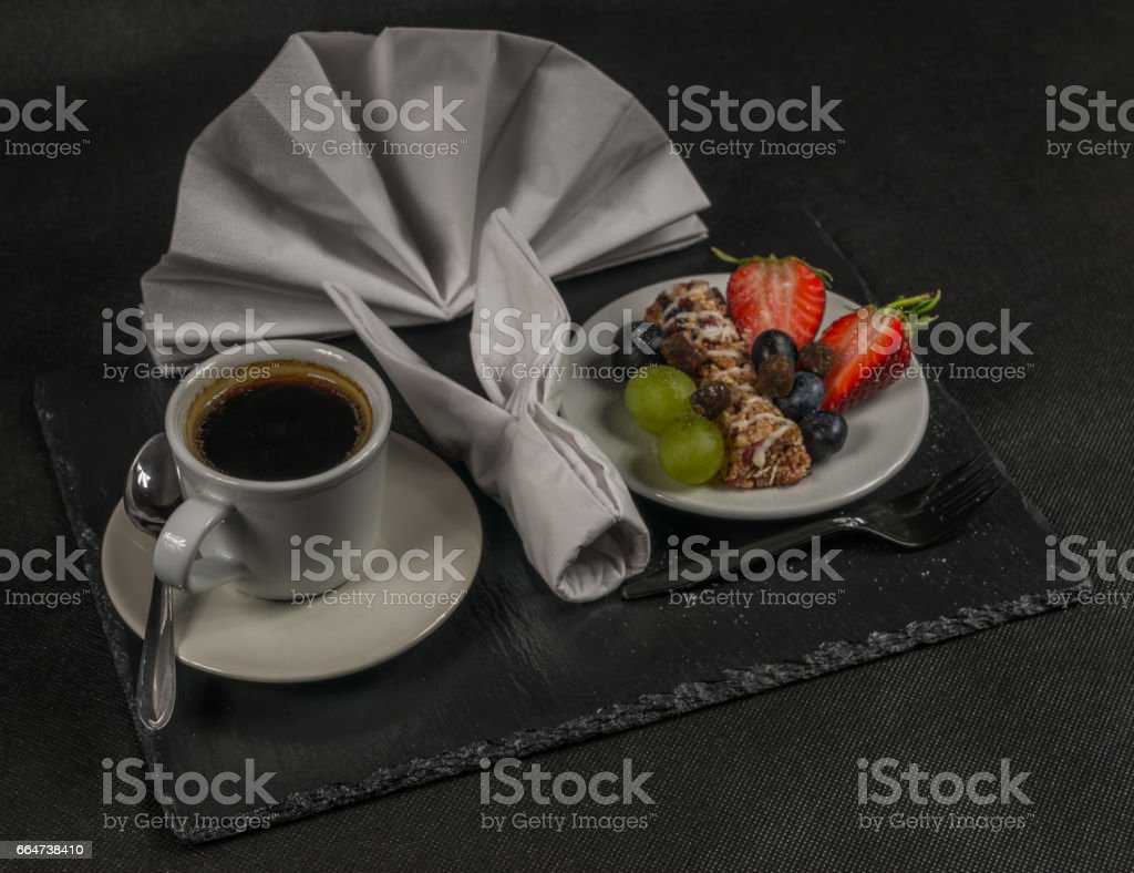 black coffee in white cup, healthy, energetic breakfast, bar whole grain, grapes, strawberries and blueberries stock photo