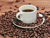 Black coffee in white mug and grains