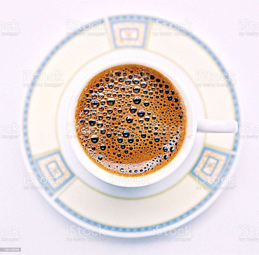 Black Coffee with Bubbles in Cup and Saucer royalty-free stock photo