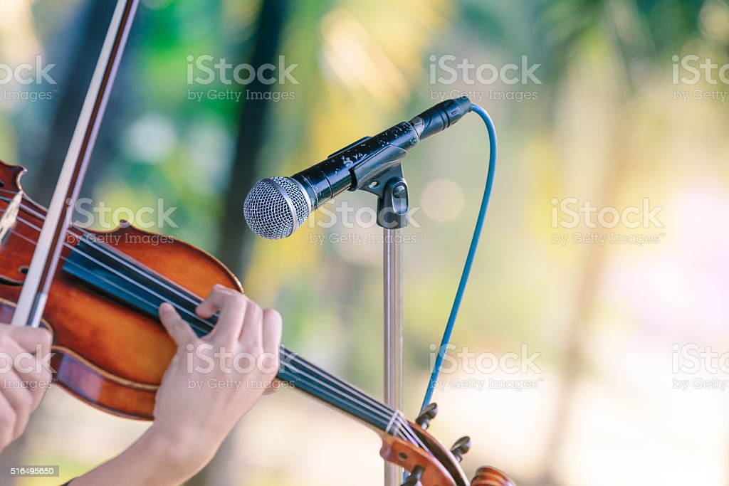Black color microphone and violin playing in outdoor concert. stock photo