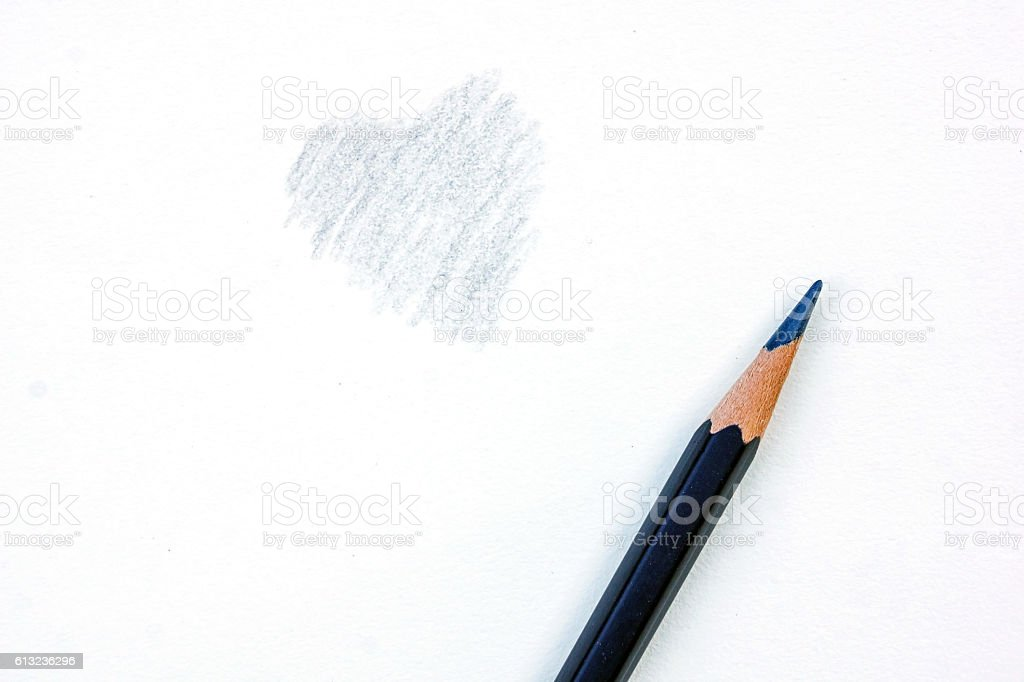 black color pencil drawing a heart on the paper drawings. stock photo
